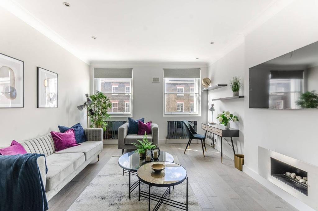Schlankes Dreisitzsofa und schlanker Sessel im modernen Wohnzimmer