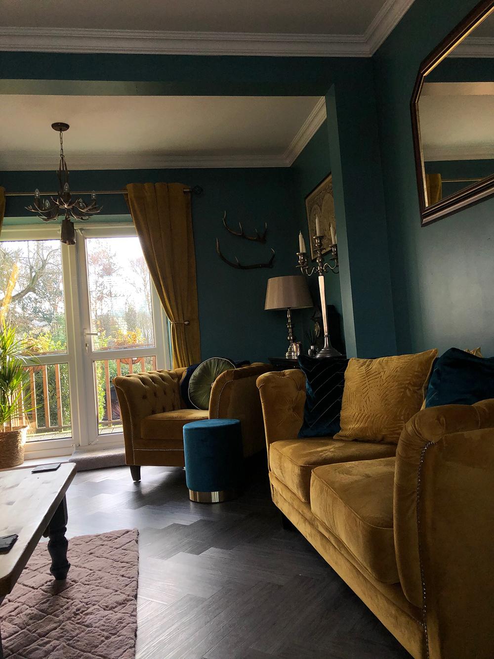 Gelbes gestepptes Sofa und Karin-Sessel im klassischen Wohnzimmer